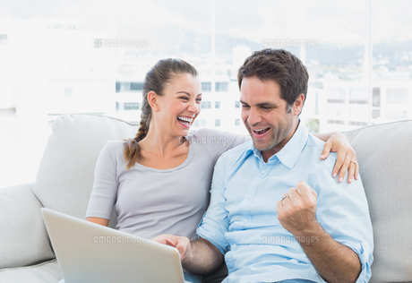 Excited couple sitting on the sofa using laptop togetherの写真素材 [FYI00001055]