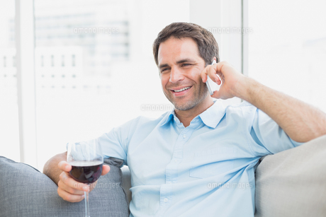 Happy man relaxing on sofa with glass of red wine talking on phoneの素材 [FYI00001056]