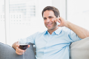 Happy man relaxing on sofa with glass of red wine talking on phoneの写真素材 [FYI00001056]