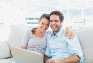 Happy couple sitting on the sofa using laptop togetherの写真素材 [FYI00001057]