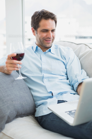 Happy man relaxing on sofa with glass of red wine using laptopの写真素材 [FYI00001058]