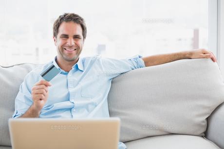 Happy man using laptop sitting on sofa shopping onlineの写真素材 [FYI00001059]