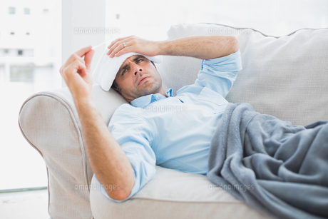 Sick man lying on sofa checking his temperature under a blanketの写真素材 [FYI00001062]