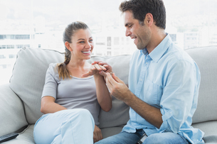 Excited couple getting engaged on their sofaの写真素材 [FYI00001069]