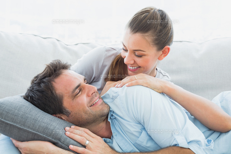 Cheerful couple relaxing on their sofa smiling at each otherの素材 [FYI00001070]