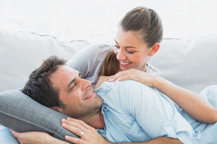 Cheerful couple relaxing on their sofa smiling at each otherの写真素材 [FYI00001070]