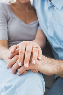 Couple showing wedding ring on womans finger on the couchの写真素材 [FYI00001071]