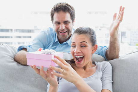 Man surprising his pretty girlfriend with a pink gift on the sofaの素材 [FYI00001072]