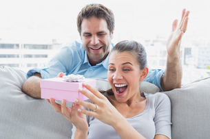 Man surprising his pretty girlfriend with a pink gift on the sofaの写真素材 [FYI00001072]