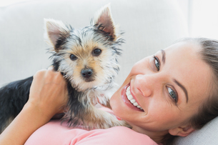 Happy woman cuddling her yorkshire terrier on the couchの写真素材 [FYI00001074]