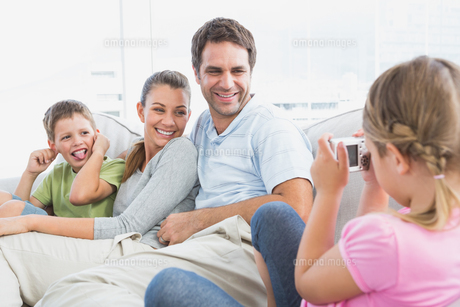 Little girl taking a photo of her family on the couchの写真素材 [FYI00001077]