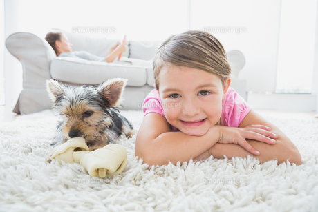 Little girl lying on rug with yorkshire terrier smiling at cameraの素材 [FYI00001084]