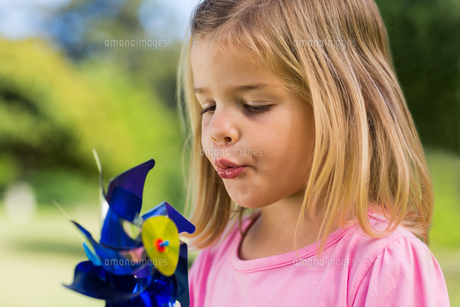 Cute girl blowing pinwheel at parkの素材 [FYI00001089]