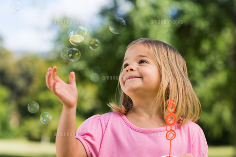 Girl looking at soap bubbles at parkの写真素材 [FYI00001091]