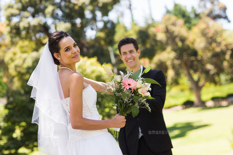 Happy newlywed couple with bouquet in parkの写真素材 [FYI00001099]