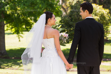 Newlywed couple holding hands and walking in parkの写真素材 [FYI00001100]