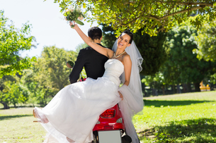 Newlywed couple sitting on scooter in parkの写真素材 [FYI00001110]