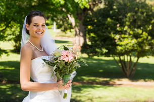 Smiling young beautiful bride with bouquet in parkの写真素材 [FYI00001112]
