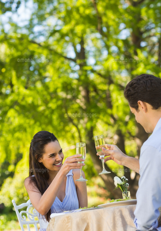Couple toasting champagne flutes at an outdoor cafテゥの写真素材 [FYI00001126]