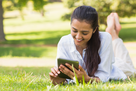 Woman text messaging while relaxing in parkの写真素材 [FYI00001133]