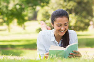 Smiling woman reading a book in parkの写真素材 [FYI00001134]