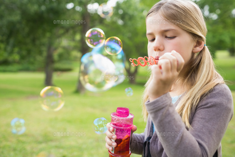 Girl blowing soap bubbles at parkの写真素材 [FYI00001135]
