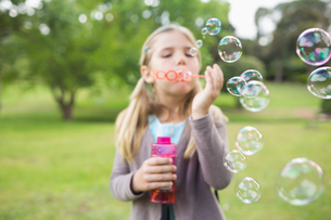 Girl blowing soap bubbles at parkの写真素材 [FYI00001136]
