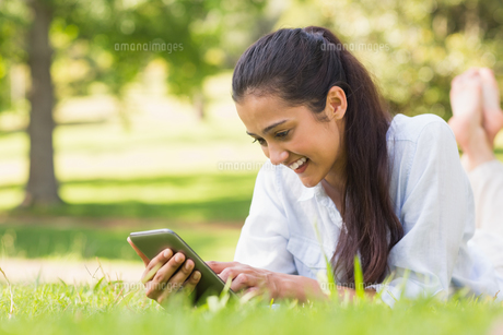 Woman text messaging while relaxing in parkの写真素材 [FYI00001137]