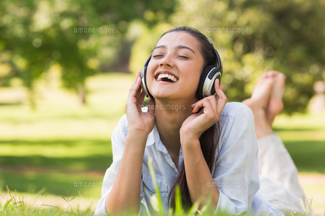 Cheerful young woman enjoying music in parkの素材 [FYI00001139]