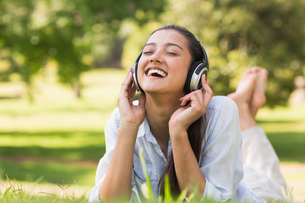 Cheerful young woman enjoying music in parkの写真素材 [FYI00001139]