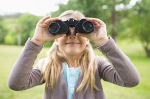 Girl looking through binoculars at parkの写真素材 [FYI00001140]