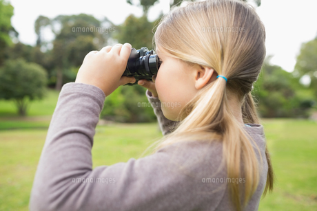 Girl looking through binoculars at parkの素材 [FYI00001141]