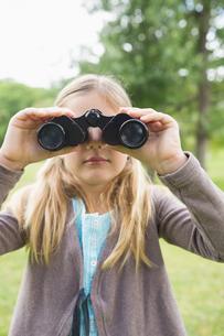 Girl looking through binoculars at parkの写真素材 [FYI00001142]