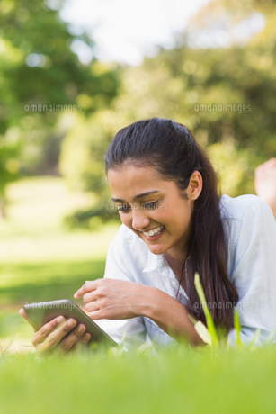 Smiling woman text messaging while relaxing in parkの写真素材 [FYI00001144]