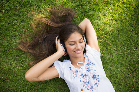 Cheerful young woman enjoying music in parkの写真素材 [FYI00001145]