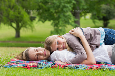 Relaxed mother and daughter lying at parkの写真素材 [FYI00001148]