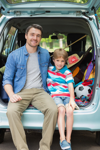 Portrait of father and son sitting in car trunkの写真素材 [FYI00001151]