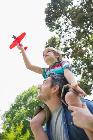Boy with toy aeroplane sitting on father's shouldersの素材 [FYI00001155]