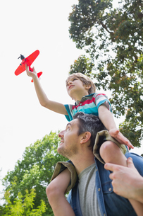 Boy with toy aeroplane sitting on father's shouldersの写真素材 [FYI00001155]