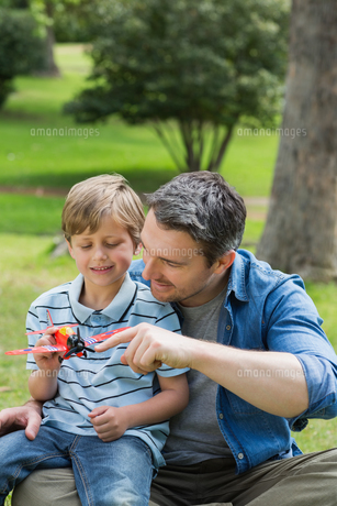 Boy with toy aeroplane sitting on father's lap at parkの写真素材 [FYI00001160]