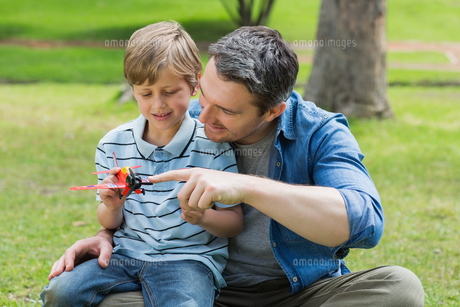 Boy with toy aeroplane sitting on father's lap at parkの写真素材 [FYI00001170]