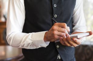 Waiter taking an order wearing a waistcoatの写真素材 [FYI00001184]