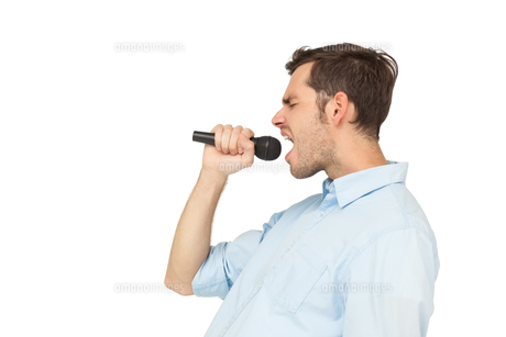 Side view of a young man singing into microphoneの素材 [FYI00001216]