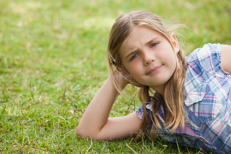 Cute young girl lying on grass at parkの写真素材 [FYI00001228]