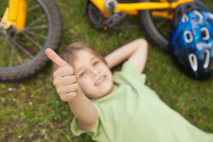 Relaxed boy gesturing thumbs up at parkの写真素材 [FYI00001234]