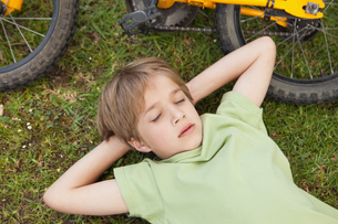 Boy resting besides bicycle at parkの写真素材 [FYI00001235]