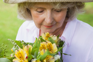 Mature woman smelling flowers at parkの写真素材 [FYI00001239]