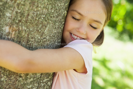 Smiling girl hugging tree with eyes closed at parkの写真素材 [FYI00001241]