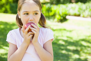 Pretty young girl eating apple in parkの写真素材 [FYI00001242]