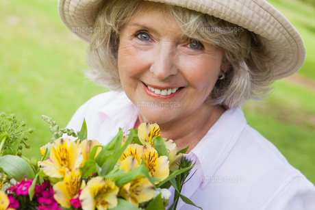 Close-up of smiling mature woman holding flowers at parkの写真素材 [FYI00001243]